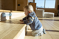 Baby boy crouching on wooden floor looking at his shadow - ZOCF000008