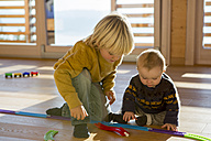 Little boy and his brother playing with toy train on the wooden floor at home - ZOCF000011