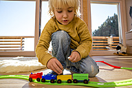 Little boy playing with toy train on the wooden floor at home - ZOCF000014