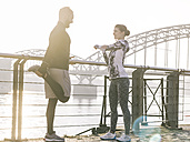 Germany, Cologne, Young couple worming up for workout, stretching - MADF000862