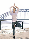 Germany, Cologne, young woman practicing yoga, tree position - MADF000874