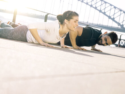 Germany, Cologne, Young couple worming up for workout - MADF000877