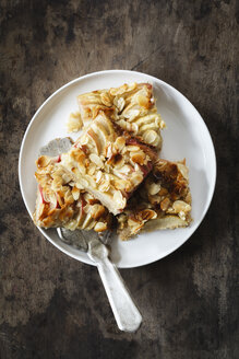 Pieces of whole meal apple pie with sliced almonds on a plate - EVGF002864