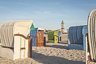 Germany, Mecklenburg-Western Pomerania, Warnemuende, beach with hooded beach chairs and lighthouse in the background - ASCF000536