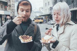 Belgium, Antwerp, young couple eating Belgian waffles on the street - RTBF000026