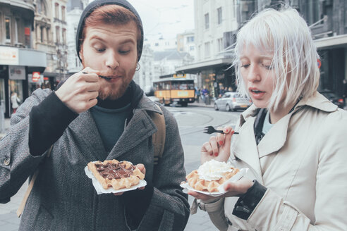 Belgium, Antwerp, young couple eating Belgian waffles on the street - RTBF000026