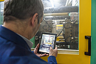 Manager doing quality assessment in plastics factory - DIGF000110