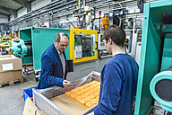 Manager and worker examining plastic products in factory - DIGF000116