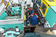 Two people in plastics factory examining machines - DIGF000122
