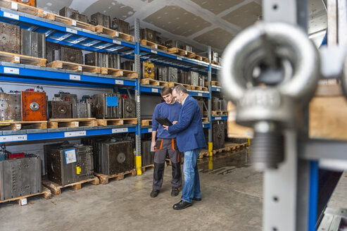 Two men examining machine blocks in storehouse - DIGF000134