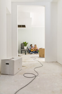 Couple with guitar relaxing on the floor of their unfinished new home - SHKF000555