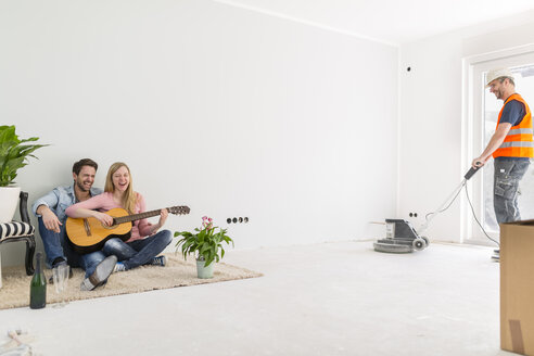 Happy couple playing guitar and singing at their new home while - SHKF000558