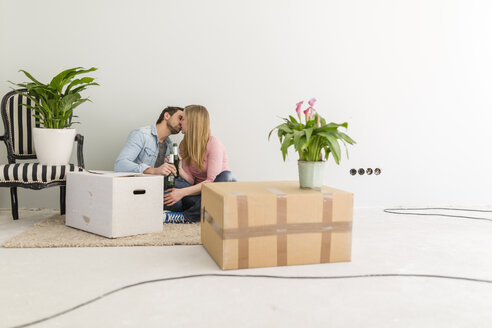 Kissing couple sitting on the floor of their unfinished new home - SHKF000564