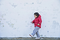Smiling little girl playing in front of a wall - ERLF000150