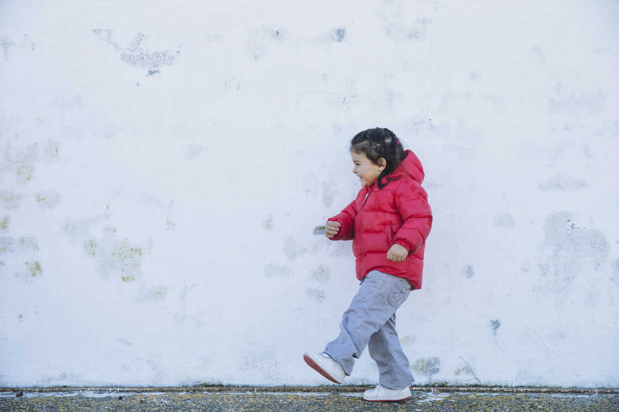 Smiling little girl playing in front of a wall - ERLF000150 - Enrique Ramos/Westend61