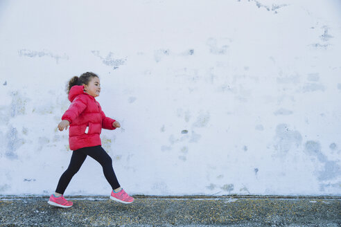 Little girl walking in front of a wall - ERLF000153