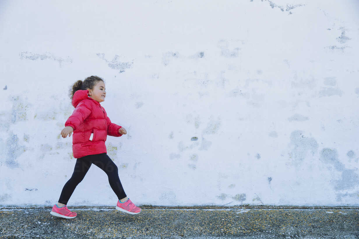Little girl walking in front of a wall - ERLF000153 - Enrique Ramos/Westend61