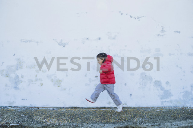 Little girl running in front of a wall - ERLF000156 - Enrique Ramos/Westend61