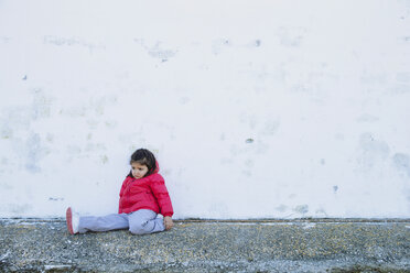 Sad little girl sitting in front of a wall - ERLF000159
