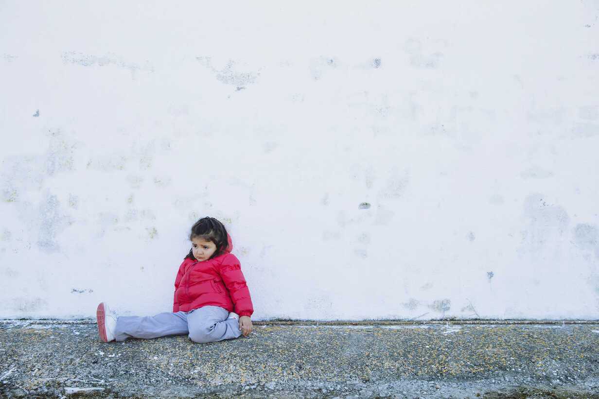Sad little girl sitting in front of a wall - ERLF000159 - Enrique Ramos/Westend61