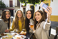 Young woman taking a selfie with her three friends at street cafe - KIJF000246