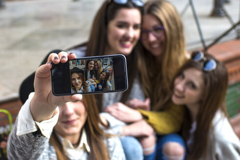 Young woman taking a selfie with her three friends, close-up - KIJF000261