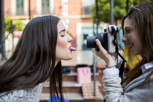 Young woman taking a picture of her friend with camera - KIJF000264