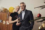 Senior couple holding bottle of Champagne on New Yera's Eve - MFF002920