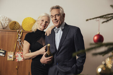 Senior couple holding bottle of Champagne on New Yera's Eve - MFF002920