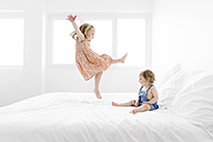 Little girl wearing summer dress jumping on a white bed while her sister watching her - LITF000194