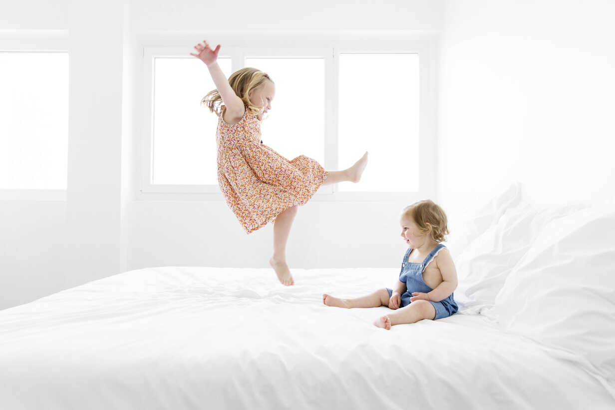 Little girl wearing summer dress jumping on a white bed while her sister watching her - LITF000194 - Lisa Tichane/Westend61