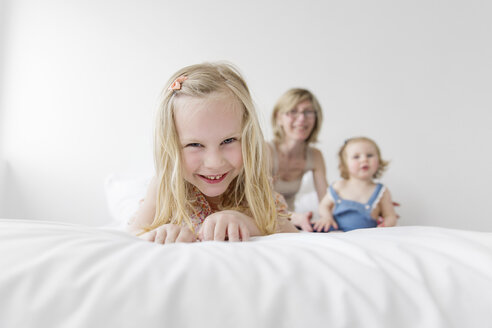 Portrait of smiling little girl on a white bed with mother and sister in the background - LITF000200