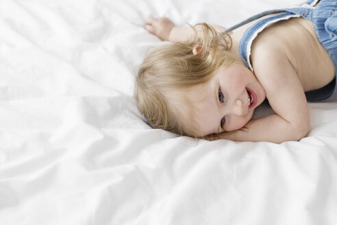 Portrait of smiling toddler girl lying on a white bed - LITF000203
