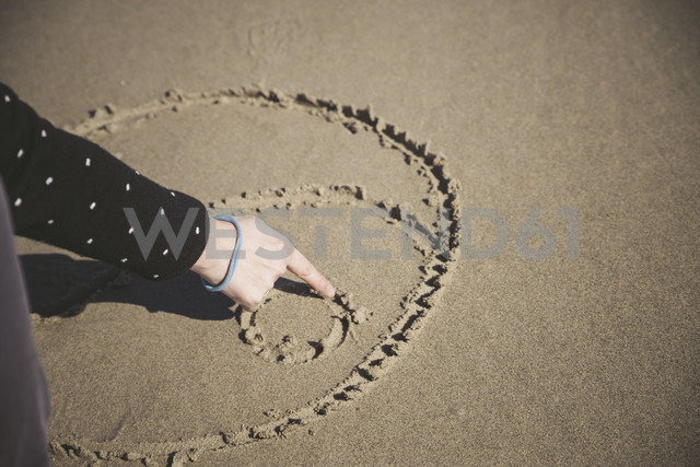 Woman scratching Yin Yang symbol in the sand of a beach, close-up - EPF000039