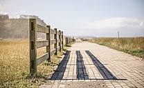 Spain, Asturias, Wooden fence and the shadow over a empty promenade - DAPF000055