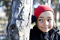 Portrait of smiling little boy hiding behind a tree trunk - VABF000377