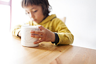 Little boy painting and decorating a mug - VABF000386