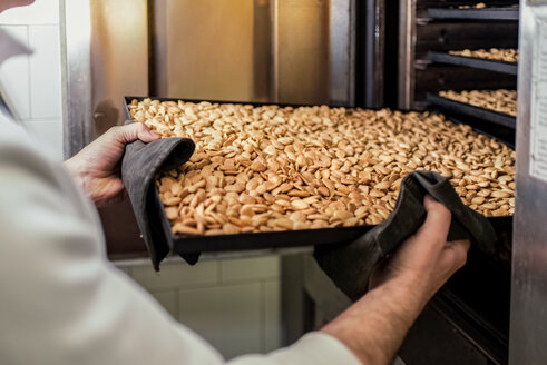 Italy, Manufacturing of traditional torrone in confectionery shop, roasted almonds on tray - CSTF001025