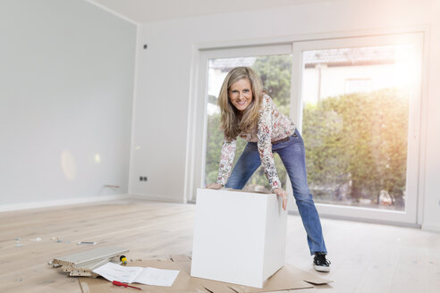 Portrait of smiling woman assembling a cabinet in a room of her new home - SHKF000584