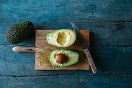 Sliced avocado on chopping board - KIJF000275