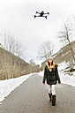 Spain, Asturias, young woman watching flying drone in the snowy mountains - MGOF001634