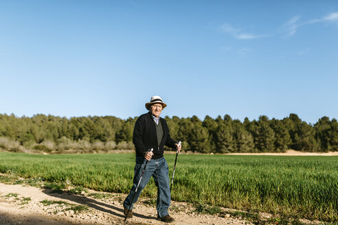 Spain, Tarragona, Senior man walking with sticks in the field - JRFF000503
