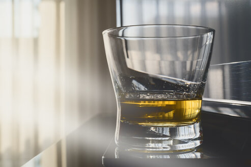 Whiskey glass in front of window, morning light and TV - FRF000404