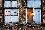 Facade of an abandoned brick house with a garland of lights - GEMF000818