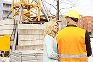 Woman looking at man with hard hat on construction site - MAEF011387