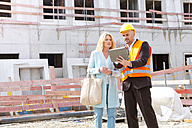 Man with hard hat talking to woman on construction site - MAEF011393