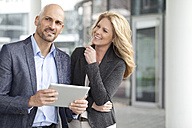 Businessman and smiling businesswoman with digital tablet outdoors - MAEF011402