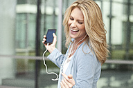 Happy woman listening to music from smartphone - MAEF011408
