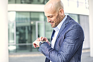 Businessman looking at smartwatch - MAEF011417