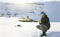 Spain, Asturias, man flying drone in snowy mountains - MGOF001675